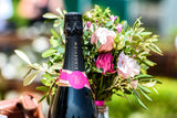 A photo of the neck of a Ridgeview Fitzrovia Rose bottle in front of a bouquet of flowers