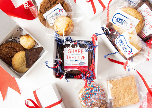 Small gift boxes arranged with various baked goods, including macaroons, brownies, blondies, and cookies.