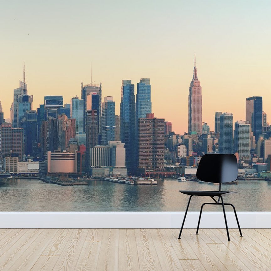 New York City sunset wallpaper mural with a Black chair sitting in front | WallpaperMural.com