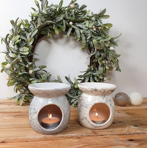 Two Ceramic Oil Burners with a lit candle inside.