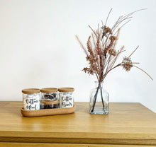 "Load image into Gallery viewer, Two large glass jars with cork lids, with wording one reading ""Cotton Wool"" and the other reading ""cotton buds"". There are also two small glass jars with cork lids stacked,  these read ""Bobbles"" and ""grips"". The wording is black but can be changed. The four jars and in a cork container so keep them organised."