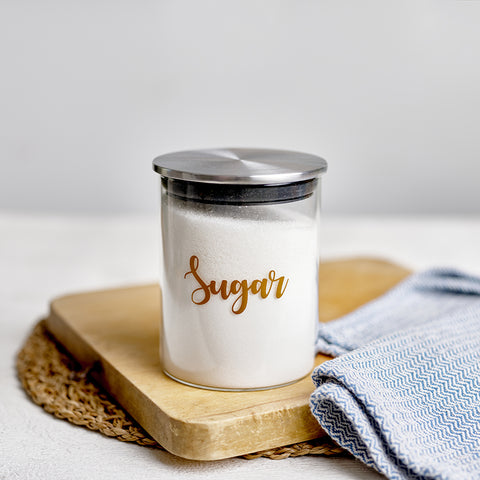 """Small glass storage jars with stainless steel lids, and custom personalised wording for """"sugar"""""""