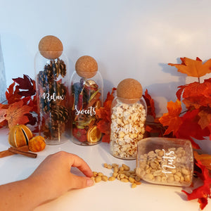 Three glass jars with cork stoppers, each different variants of size, with custom personalised wording on the face of the jar, all containing beautiful autumn supplies.