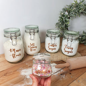 "Glass Clip Top Jar Baking Bundle Set, contains four glass jars, saying ""Plain Flour"", ""Self Raising Flour"", ""Caster Sugar"" and ""Icing Sugar"". Also contains a free smaller glass jar with clip top, with the words ""Sprinkles"" on it."
