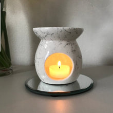 Load image into Gallery viewer, The ceramic oil burner with a marble effect, with a burning candle inside of it, melting the oil in the top.
