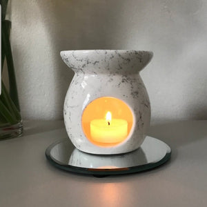 The ceramic oil burner with a marble effect, with a burning candle inside of it, melting the oil in the top.
