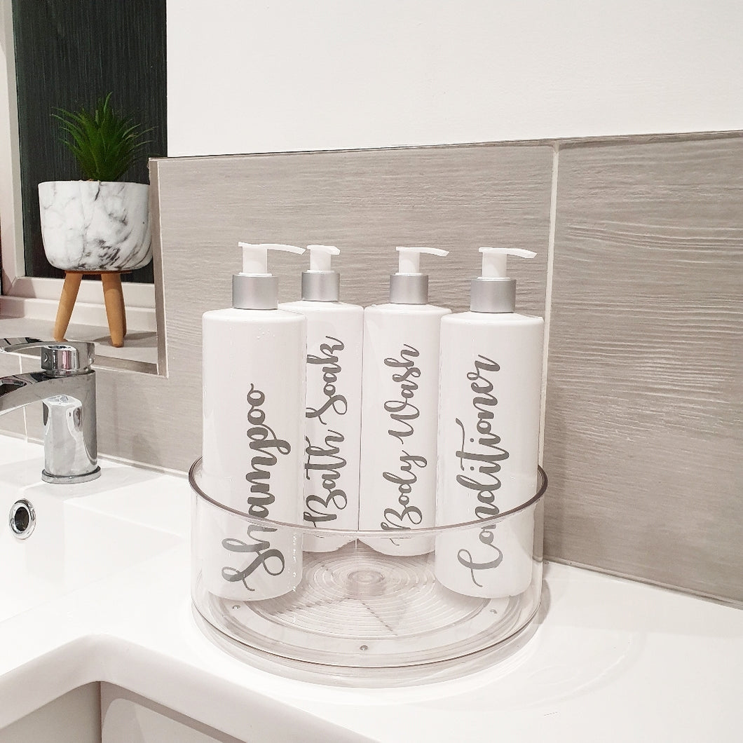 Four Reusable dispenser bottles in a lazy Susan with custom personalised wording.