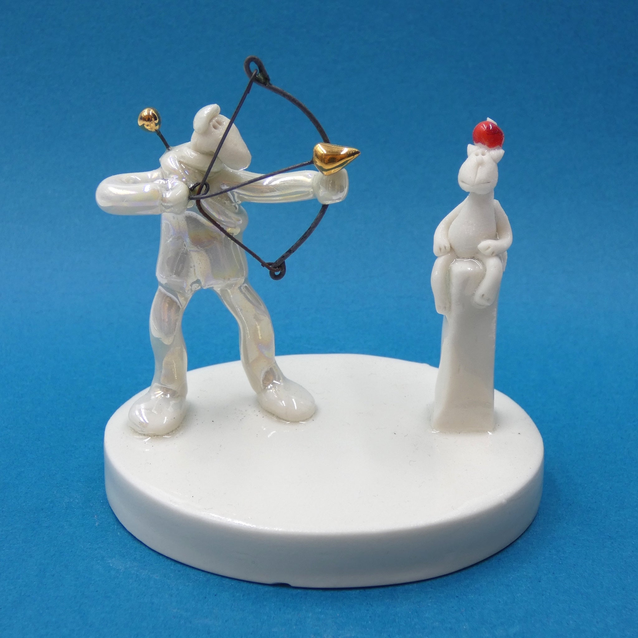Porcelain sculpture of an archer and his brave cat by artist Andrew Bull
