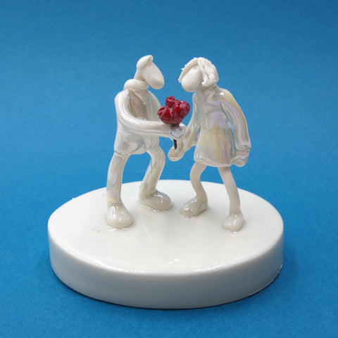 Porcelain sculpture of a man giving a woman roses by artist Andrew Bull
