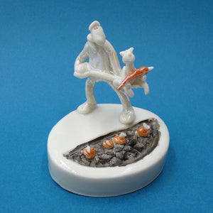 Porcelain sculpture of a man tending the carrots with help from his cat by artist Andrew Bull