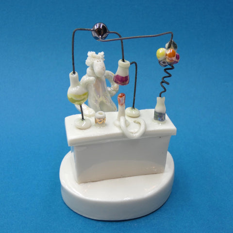 Porcelain sculpture of a scientist conducting an experiment by artist Andrew Bull