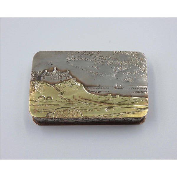 Metal hinged box depicting a cottage overlooking a pebble beach by artist Cornelius Van Dop