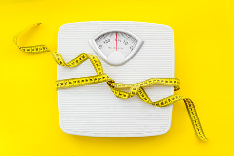 Can CBD help you lose weight? scale with a tape measurer wrapped around.