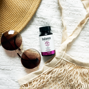 TerraVita Balance CBD capsules on a white sheet with a pair of sunglasses next to them.