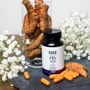 TerraVita Ease CBD Capsules for joint support, inflammation and pain. Bottle with capsules spilling out next to turmeric.