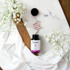 Load image into Gallery viewer, TerraVita Balance CBD Capsules spilling out onto marble tray with white flowers and white sheet.