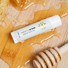 Load image into Gallery viewer, TerraVita CBD Hydrating Lip Balm with 100mg Broad Spectrum CBD and Manuka Honey next to a bar of honey and wooden stick.
