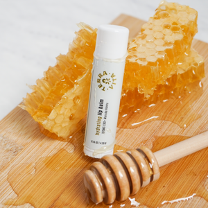 TerraVita CBD Hydrating Lip Balm with 100mg Broad Spectrum CBD and Manuka Honey next to a bar of honey and wooden stick.