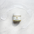Load image into Gallery viewer, TerraVita CBD moisturizing body butter with 500mg of CBD, Manuka Honey, Hyaluronic acid and vitamin C spread out on marble floor.