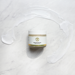 TerraVita CBD moisturizing body butter with 500mg of CBD, Manuka Honey, Hyaluronic acid and vitamin C spread out on marble floor.