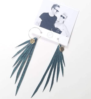 Open image in slideshow, Teal blue/green snakeskin leather fringe earrings on delicate gold hoop with small hexagon logo charm made from raw brass. Hanging from earring card with black and white image of artist woman and her dude dressed up.