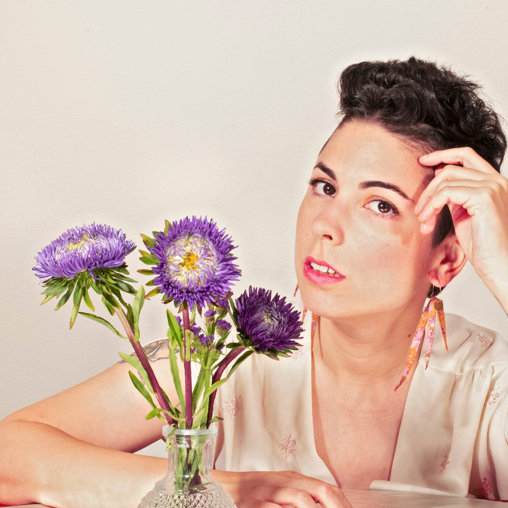 Female model with short brown hair wears a cream silk blouse and sits at a table with a vase of purple flowers in front of her. She is modeling tan suede layered boho style fringe earrings on 20mm gold hoops with small gold colored brass hexagon charm