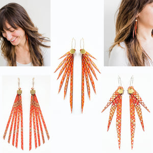 collage of the three styles of red and gold snakeskin embossed leather earrings from the Mombi Ltd Edition collection. Also shown are two images of a female model wearing the Rebel style of the collection.  Layered fringe, or tassel style earrings describe the shapes. They are on gold colored hoops with hexagon charms. The edges of the earrings are angled and pointy but the leather is soft. They are pretty rockin' earrings.