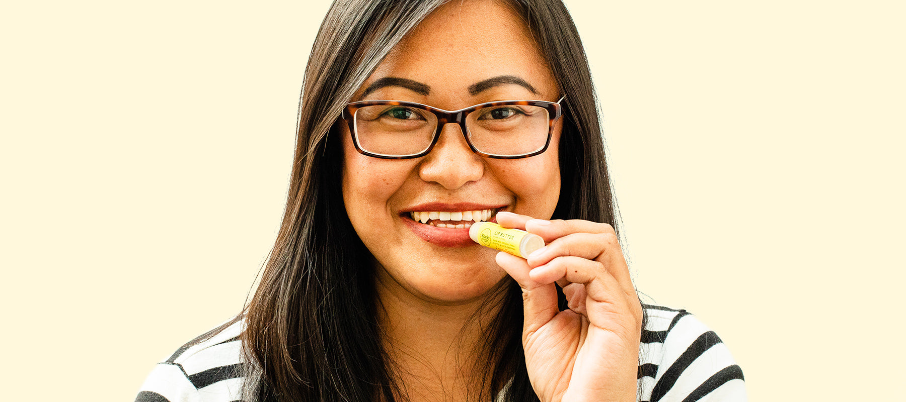 image of woman applying all natural rocky mountain soap company lip balm to her lips.