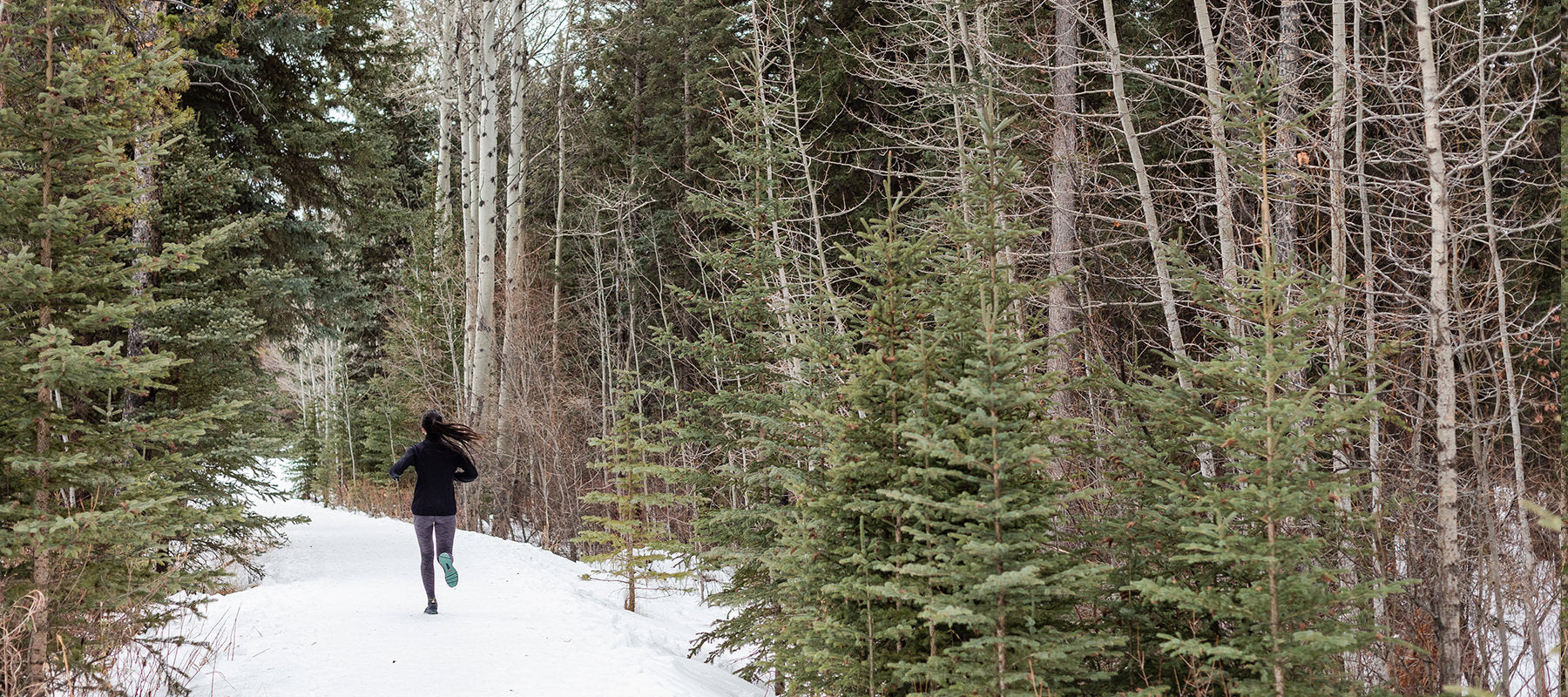 Woman running through the woods with snow.