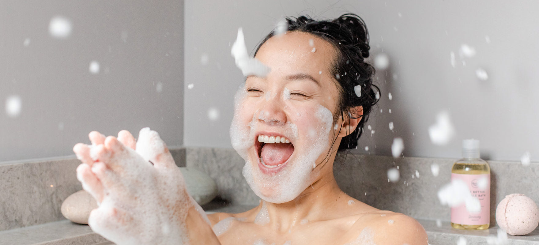 Woman laughing and clapping her hand throwing bubbles everywhere in the bath using SLS-free all-natural bubble bath from Rocky Mountain Soap Company
