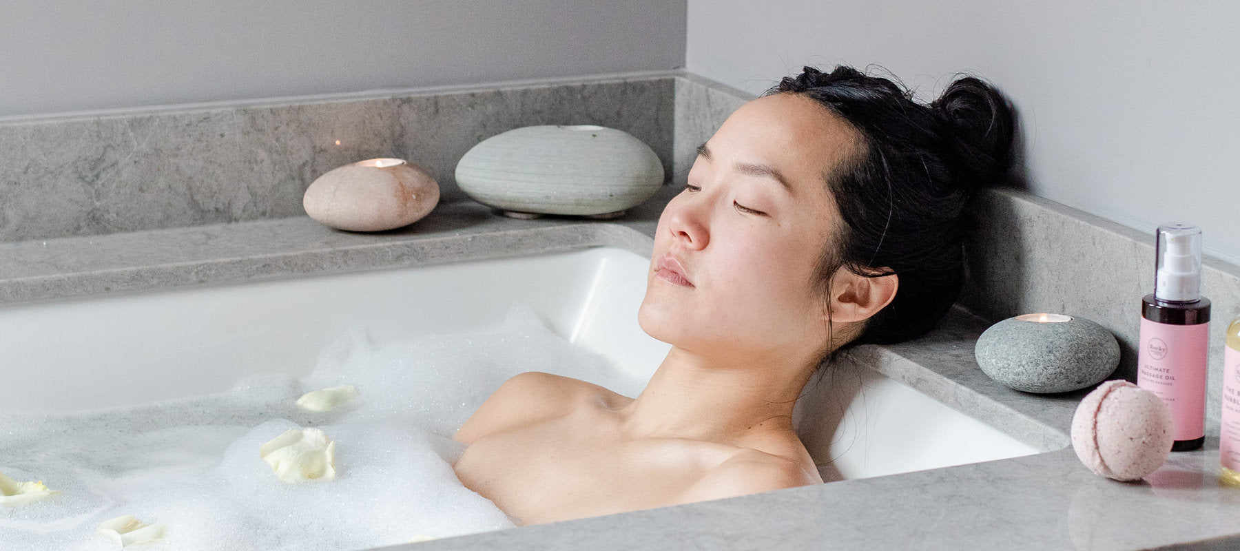 Woman lying in the bath with her eyes closed. There are all-natural sulfate free bubbles from Rocky Mountain Soap Company, a bath bomb and massage oil on the side of the tub.
