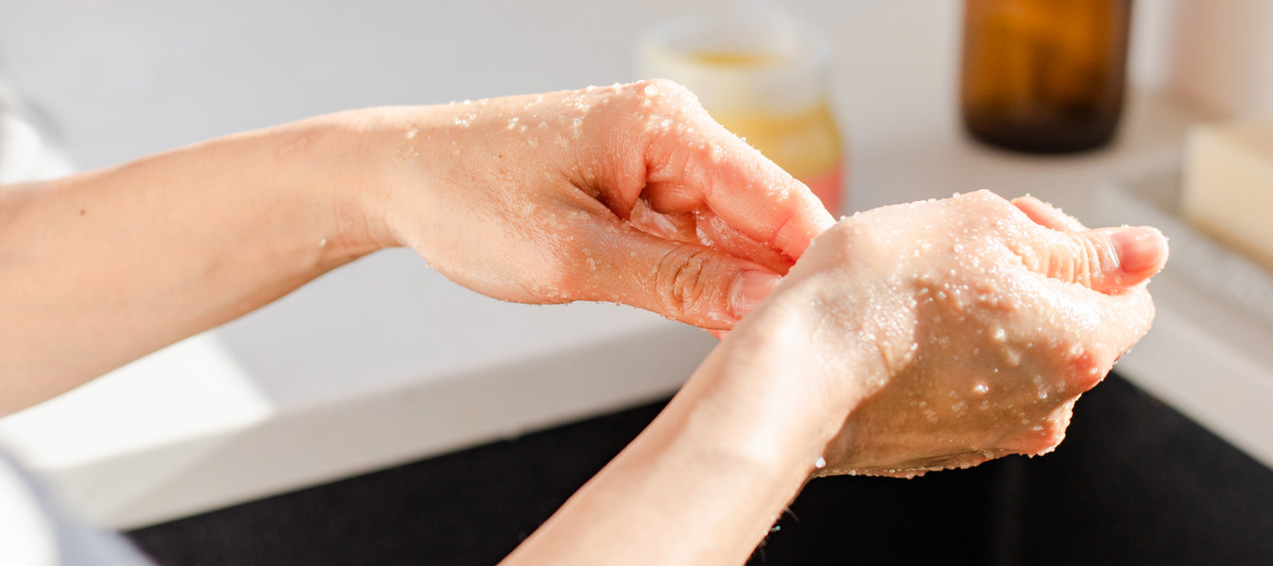 Hands over a sink exfoliating with Rocky Mountain Soap Company body scrub.