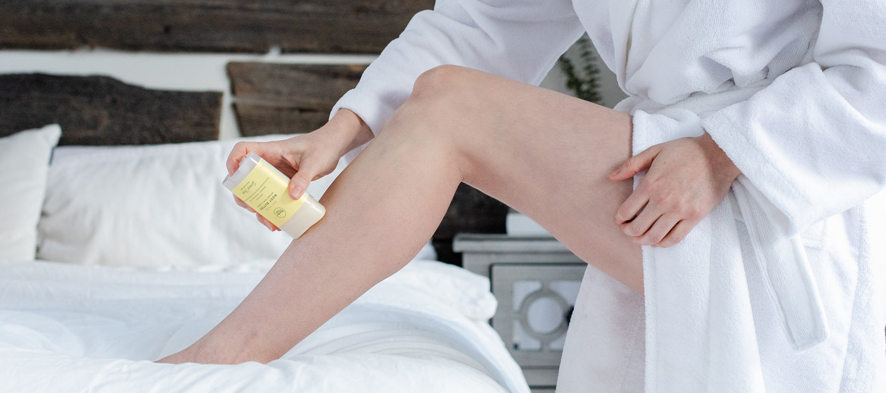 Image of person in white robe in one leg up on the bed applying body butter to leg.