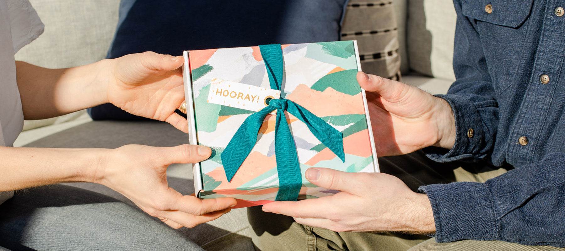 Two people exchange an all-natural, made in Canada gift set from Rocky Mountain Soap Company this holiday season.