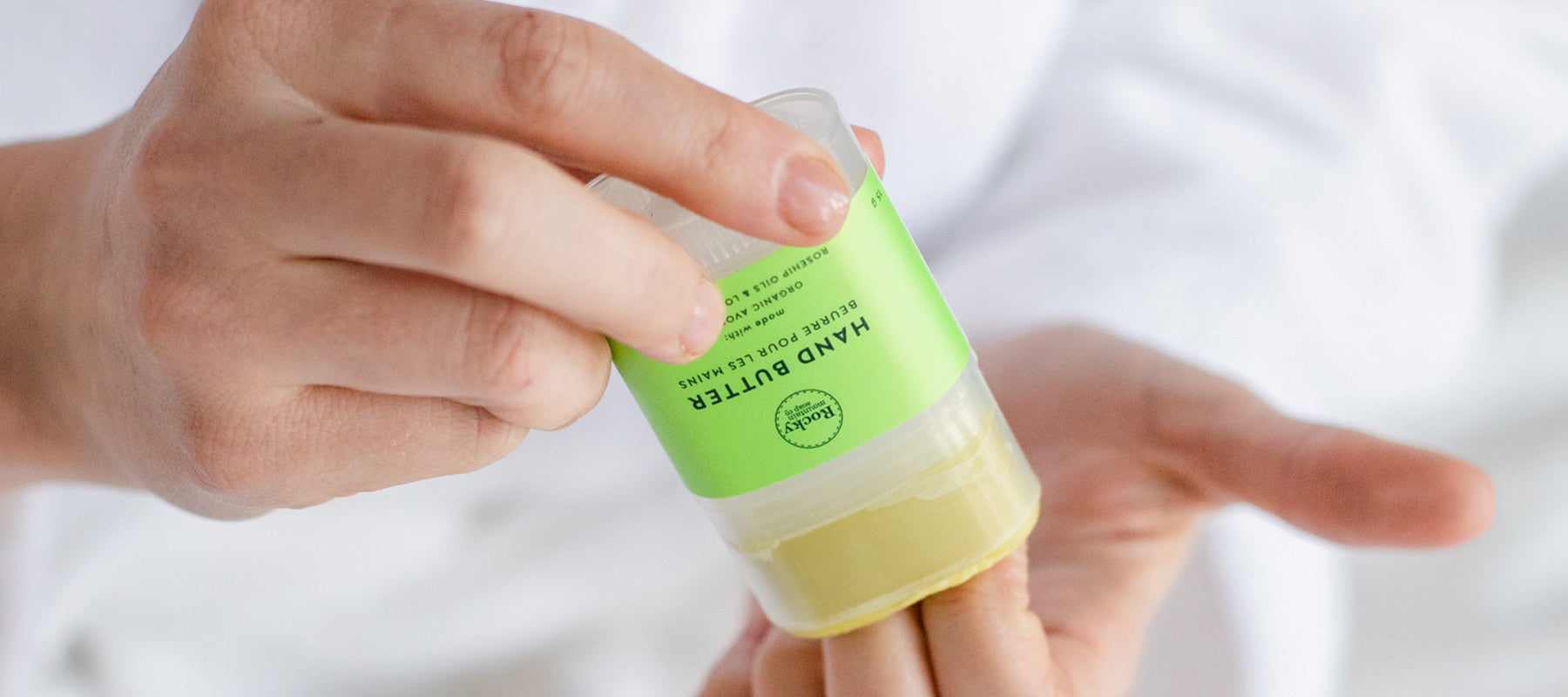 Image of hands rubbing moisturizing organic hand butter onto cuticles.