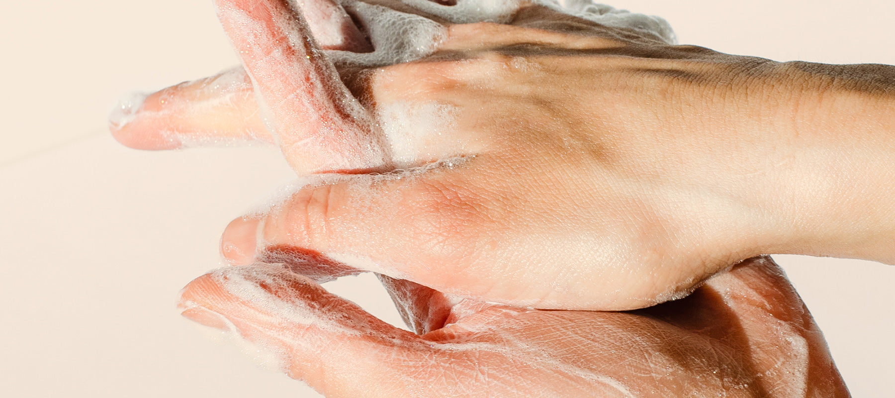 Hands washing with soap all natural lather on a peach background.