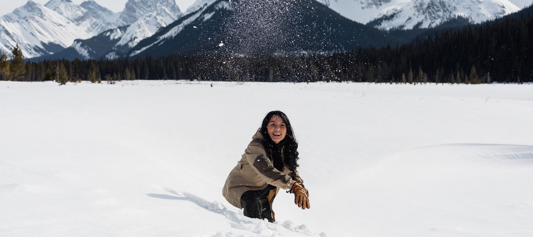 Woman throwing snowball with mountains in the background.