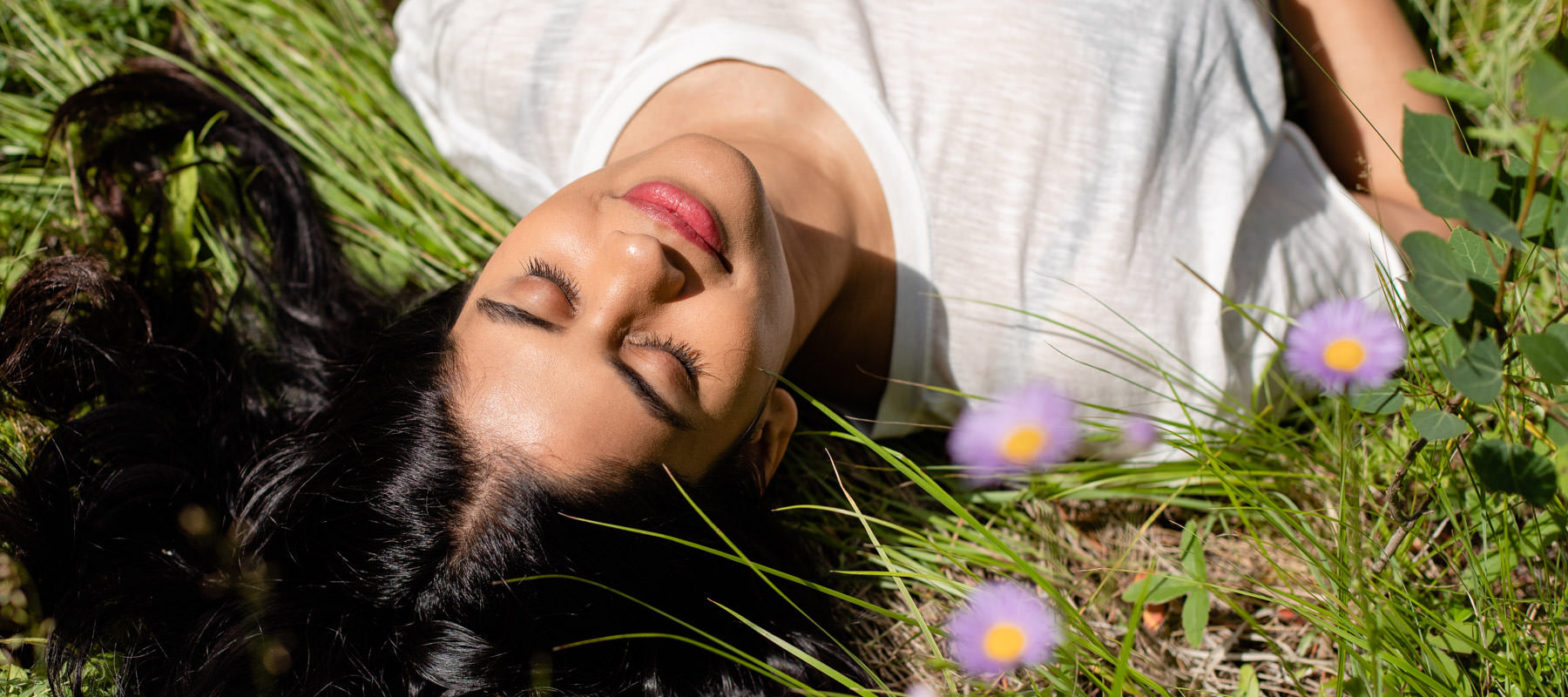woman lying in the grass and wildflowers.