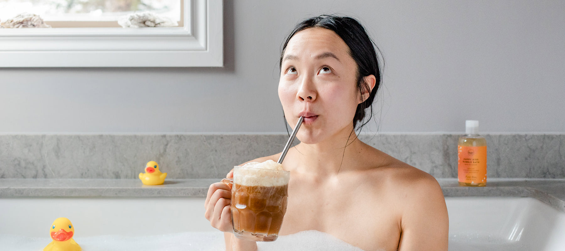 Woman in the bath drinking a root beer float with a bottle of all natural sls-free root beer scented bubble bath and rubber duckies in the background.