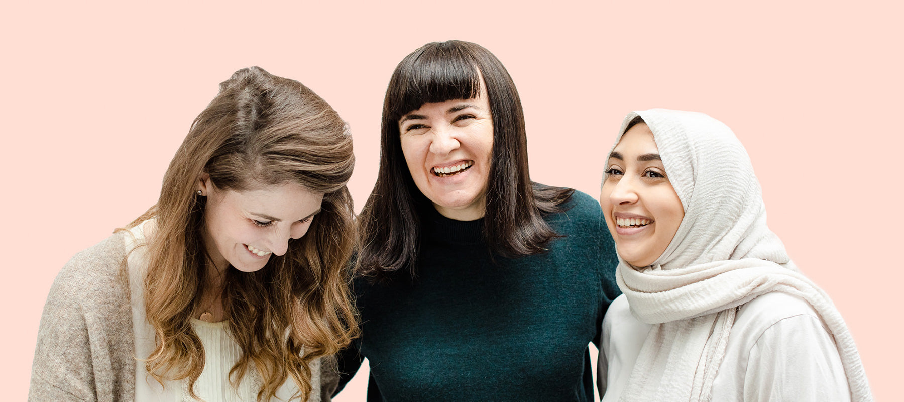 Three women, one with long light brown hair, one with dark hair and bangs, and one wearing a hijab, stand together laughing on a peach background.