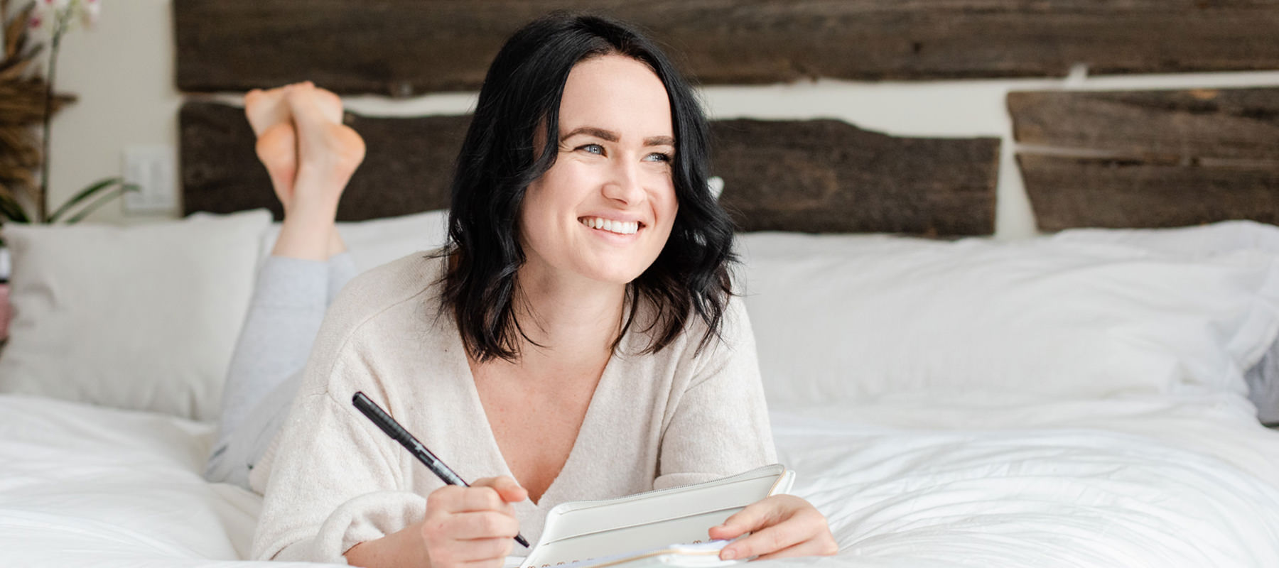Woman lying on white bed spread writing in her journal.