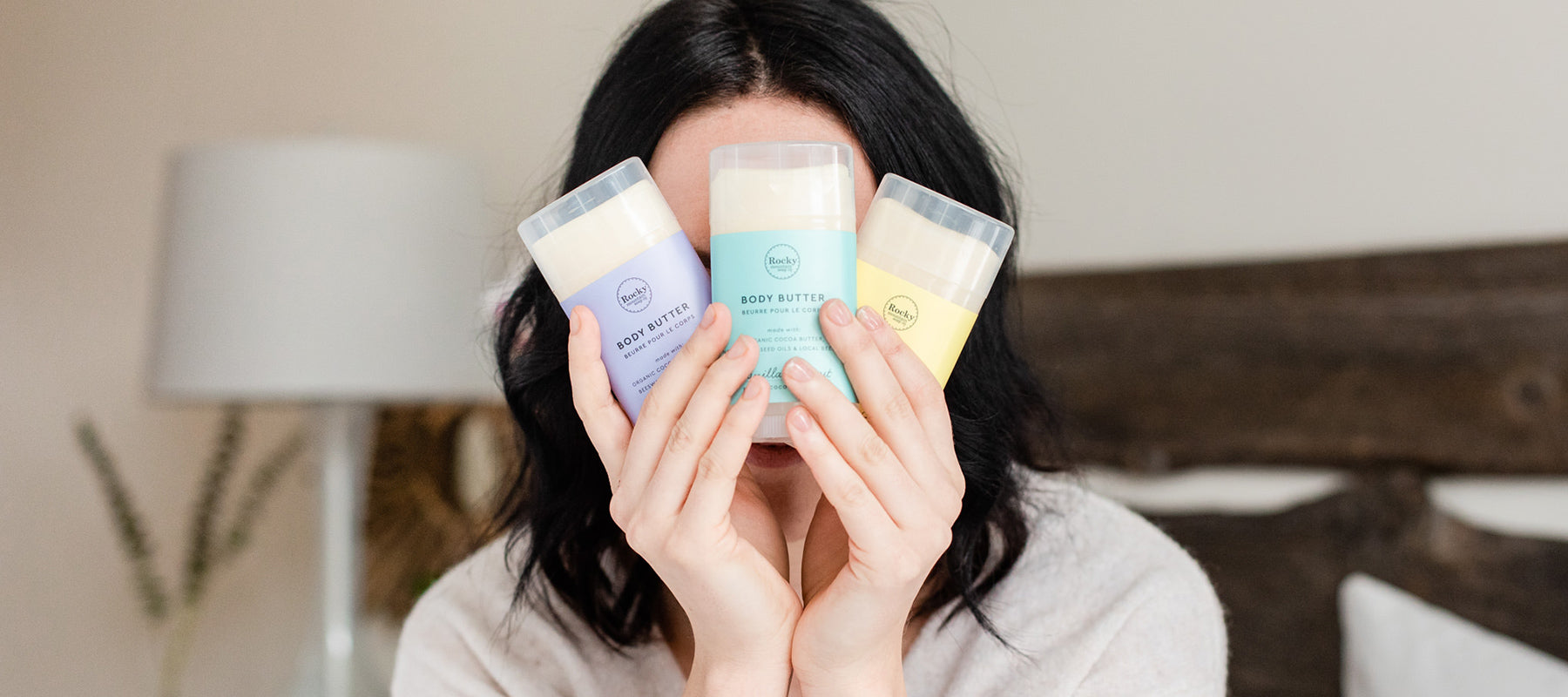 Woman holding up three all natural organic Rocky Mountain Soap Company body butters made with local Canadian beeswax.