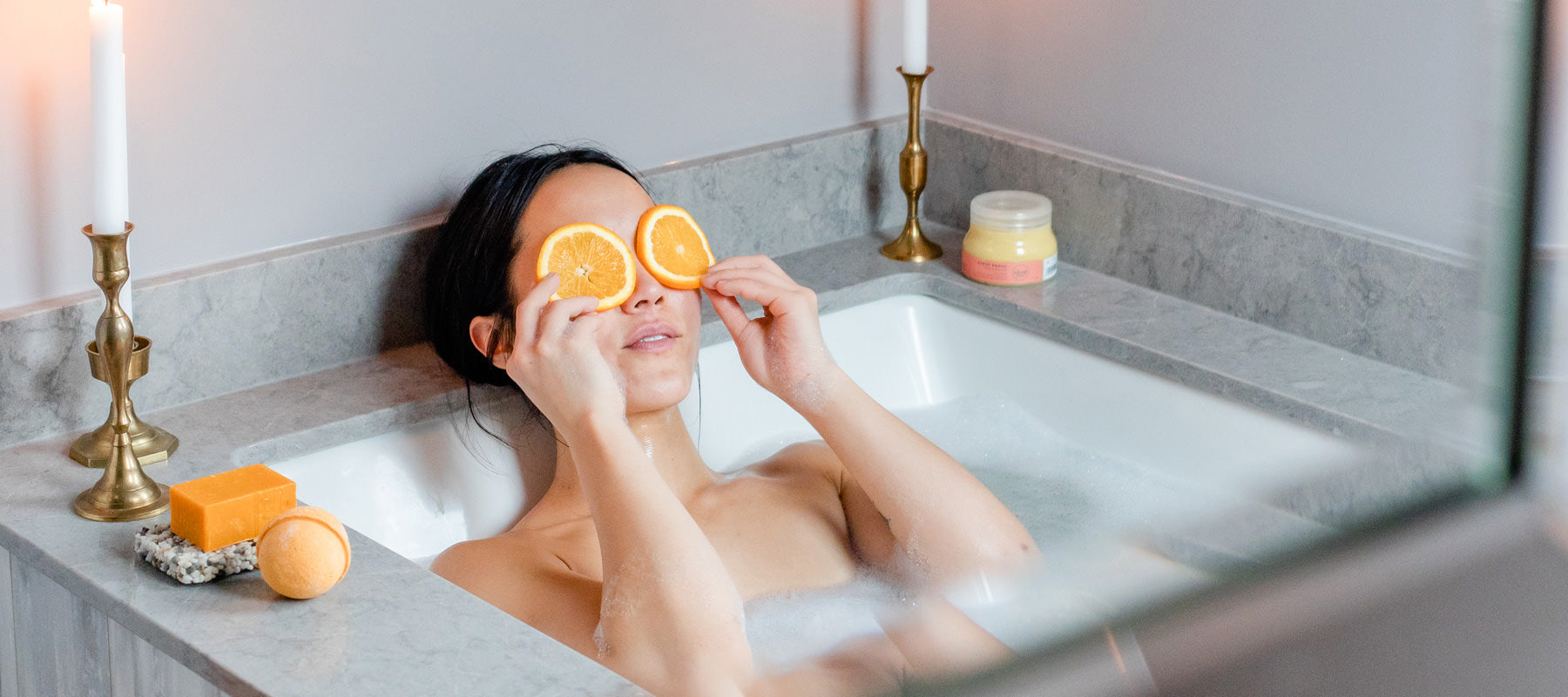 Woman in bath with orange slices on her eyes. On the side of the tub are Canadian local Rocky Mountain Soap Company natural bar soap, bath bomb and body scrub.