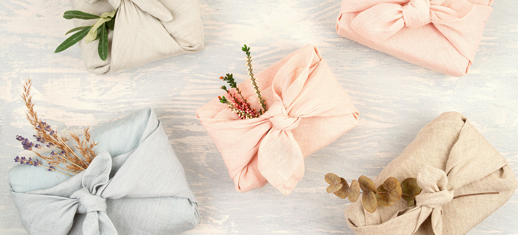 Five multicoloured cloths are artfully wrapped around gifts as a way to reduce landfill waste around the holidays from excess gift wrapping. These furoshiki wraps are an eco-friendly gift wrapping idea.