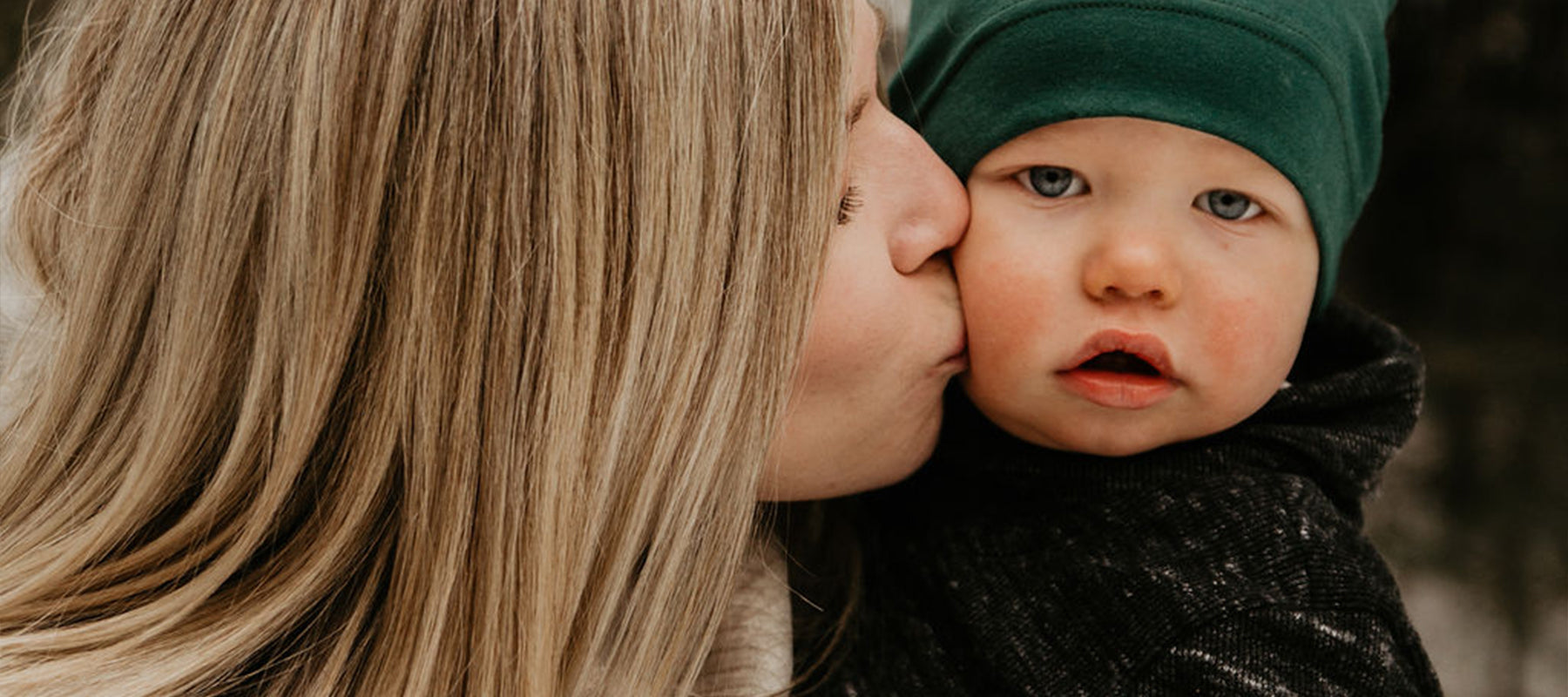 picture of mother kissing baby's cheek.
