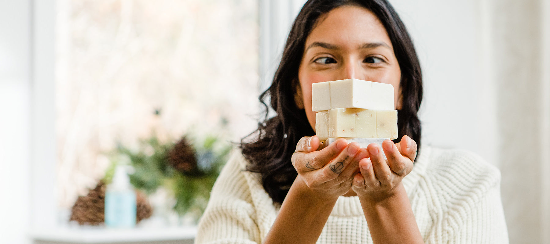 Image of a woman holding a stack of natural bar soap from Rocky Mountain Soap Company