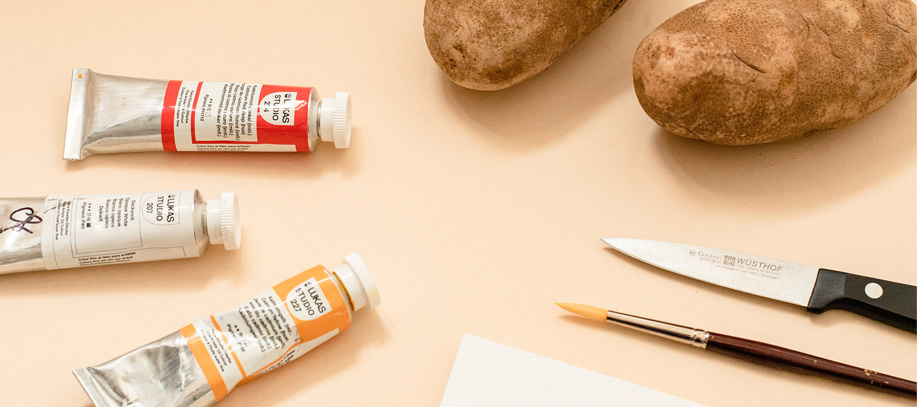 Image of paint, paint brush, potatos, knife and paper to make a DIY holiday card potato stamp.