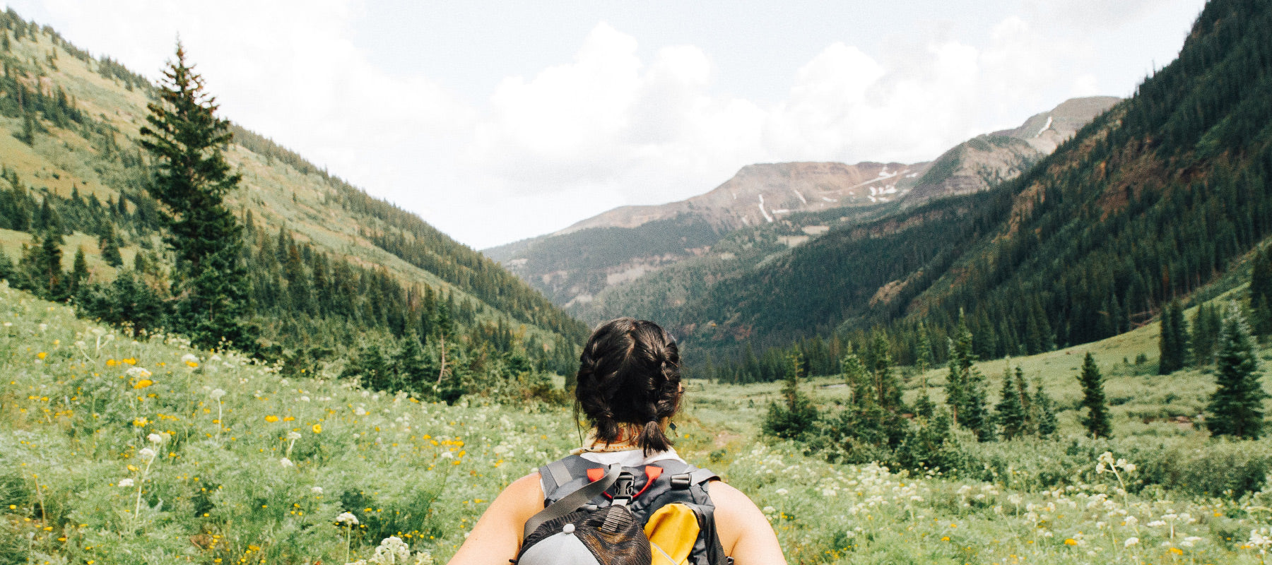 woman with a backpack hiking in the mountains