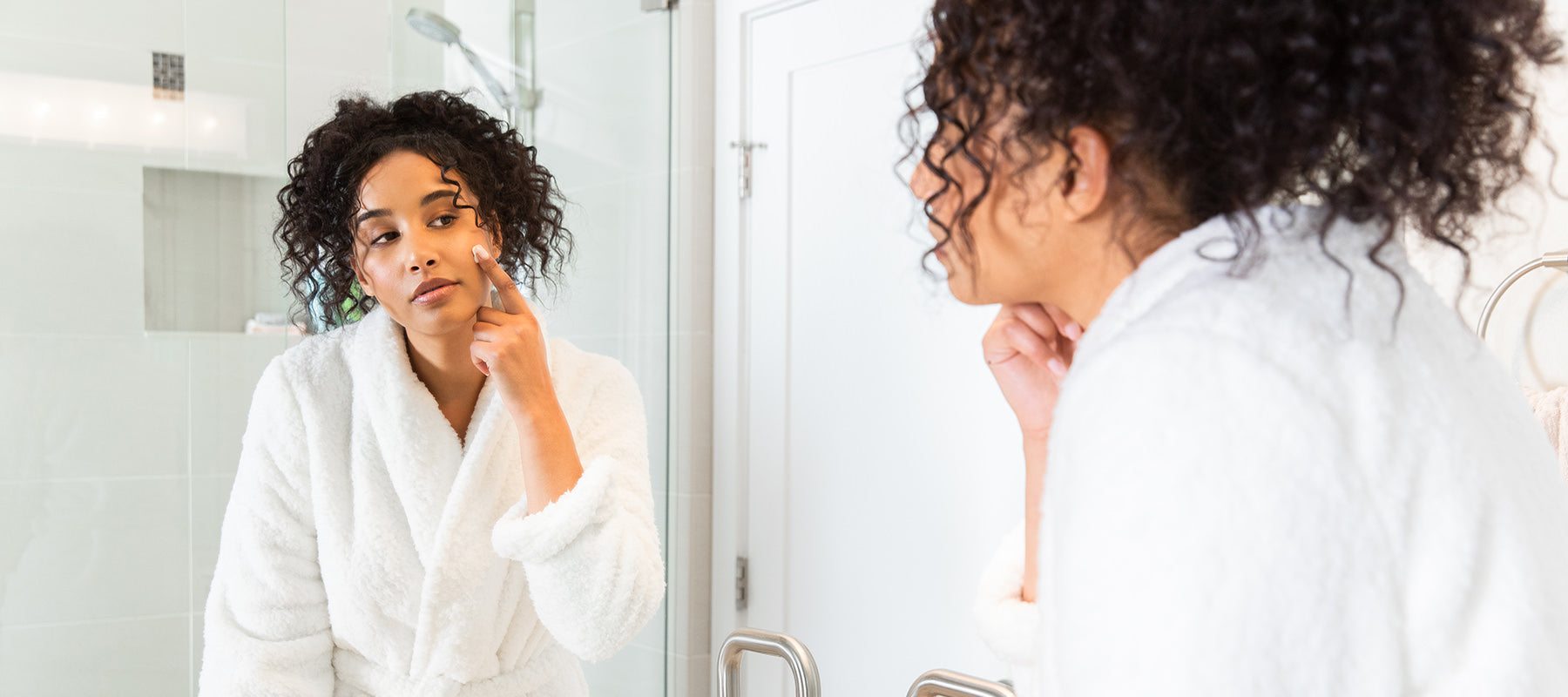 image of women using natural face cream looking in the mirror.