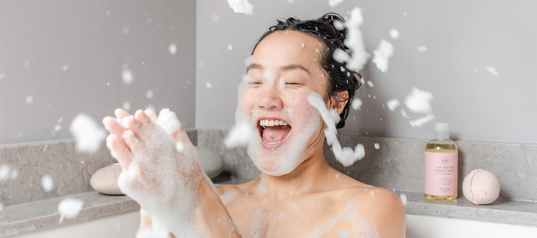 Woman clapping bubbles together laughing in bath.